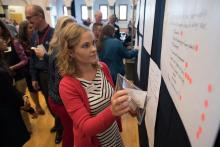 a participant in President Robbins' strategic planning process adds a post-it to a whiteboard